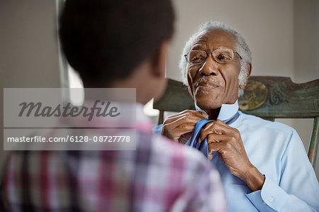 Grandfather tying necktie