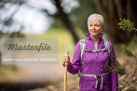 Portrait of a mature woman enjoying a peaceful hike along a forest trail.