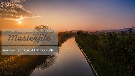The Shropshire Union canal leads through the Cheshire plain to Beeston Castle and the Peckforton sandstone ridge at sunrise, Cheshire, England, United Kingdom, Europe