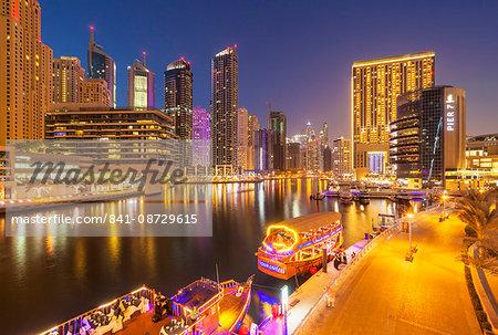 Dubai Marina skyline and tourist boats at night, Dubai City, United Arab Emirates, Middle East