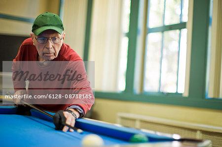 Senior man playing a game of pool.