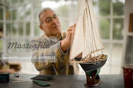 Senior man working on a model boat inside his garage.