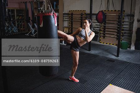 Female boxer kicking punching bag in fitness studio