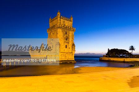 Illuminated Torre de Belem on Tejo River at Dusk in Lisbon, Portugal