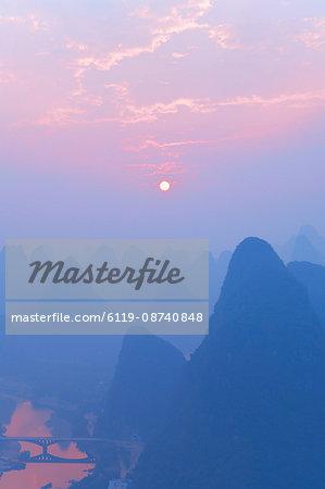 Karst landscape, Li Jiang (Li River) and rising sun, Yangshuo, Guangxi Province, China, Asia