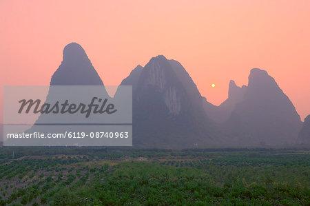 Karst landscape and setting sun, Yangshuo, Guangxi Province, China, Asia