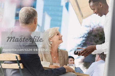 Business people watching waiter using credit card machine at urban sidewalk cafe