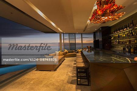 Twilight ocean view beyond luxury home showcase bar