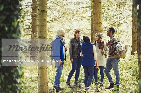 Friends talking hiking in sunny woods