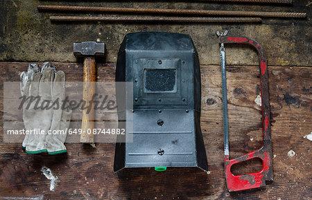 Gloves, hammer, welding visor, saw
