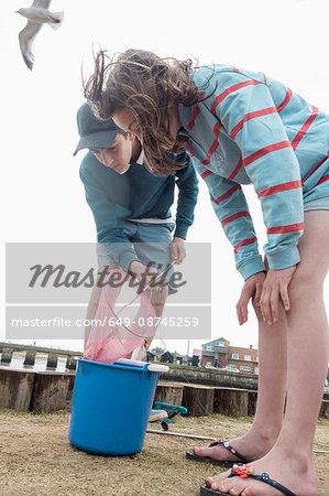 Boy and girl emptying fishing net into bucket