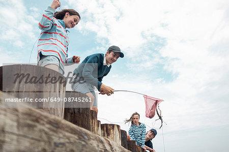 Children fishing on pier, Southwold, Suffolk, UK