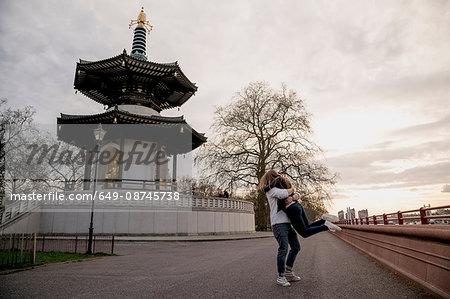 Romantic young man lifting girlfriend in Battersea Park, London, UK
