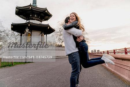 Happy young man hugging girlfriend in Battersea Park, London, UK