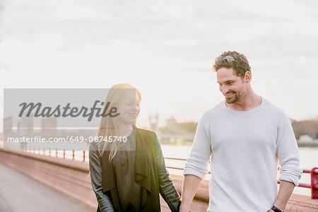 Romantic couple strolling on waterfront at sunset, Battersea Park, London, UK
