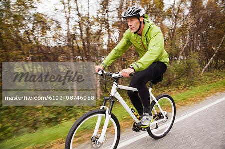 Mature man setting riding mountain bike along country road