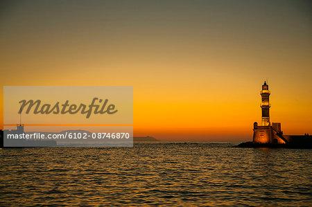 Illuminated lighthouse at sunset