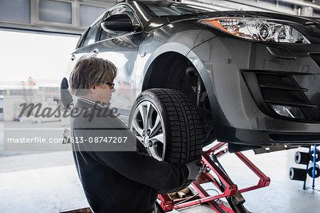 Mechanic adjusting tire on car at workshop