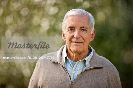Senior man standing outside.