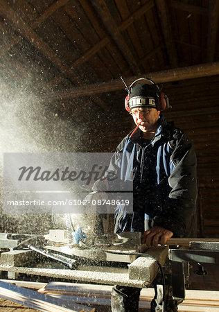 Carpenter cutting plank inside barn