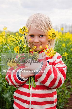 Girl holding oilseed rape flowers