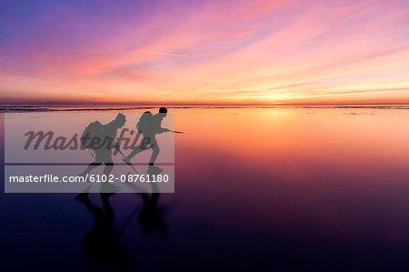 People long-distance skating at sunset, Vanern, Sweden