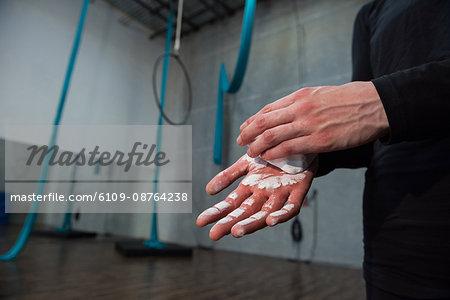 Gymnast rubbing chalk powder on her hands in fitness studio