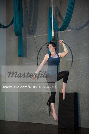 Gymnast performing gymnastics on hoop in fitness studio