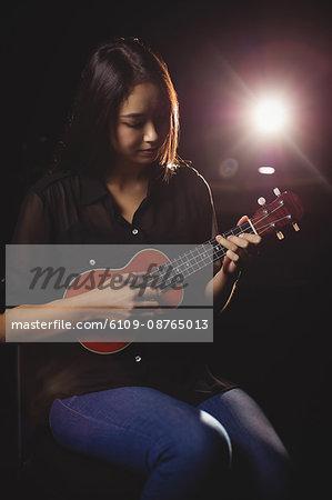 Beautiful woman playing a guitar in music school