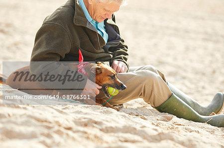 Man and dog sitting on beach, Constantine Bay, Cornwall, UK