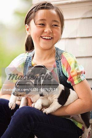 Girl holding three puppies.