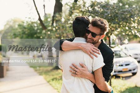 Young male couple hugging on suburban sidewalk
