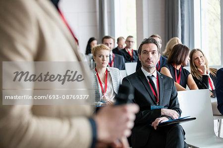 Businessman looking at public speaker during seminar