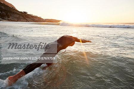 Male triathlete swimmer in wet suit diving into ocean
