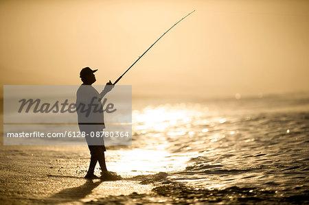 Silhouette of a man fishing near the sea.