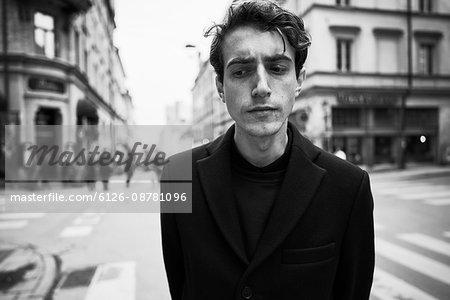 Sweden, Stockholm, Sodermanland, Sodermalm, Gotgatan, Young man wearing black jacket in street