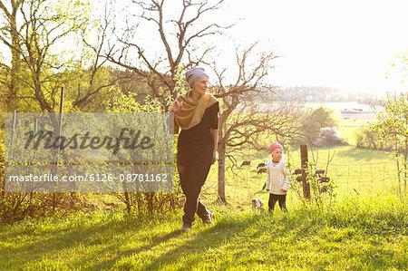 Sweden, Sodermanland, Jarna, Woman walking with grandson (2-3) in pasture
