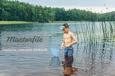 Sweden, Smaland, Mortfors, Kappemalagol, Boy (8-9-) wading and fishing