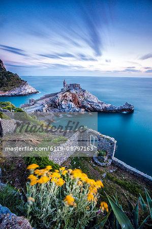 Flowers and blue sea frame the old castle and church at dusk, Portovenere, UNESCO World Heritage Site, La Spezia Province, Liguria, Italy, Europe