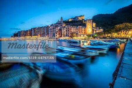 View of blue sea and boats surrounding the colorful village at dusk, Portovenere, UNESCO World Heritage Site, La Spezia Province, Liguria, Italy, Europe