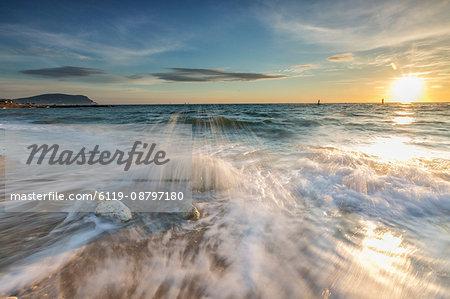Waves crashing on the sandy beach framed by sunrise, Porto Recanati, Province of Macerata, Conero Riviera, Marche, Italy, Europe