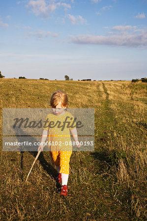 Girl walking through pasture