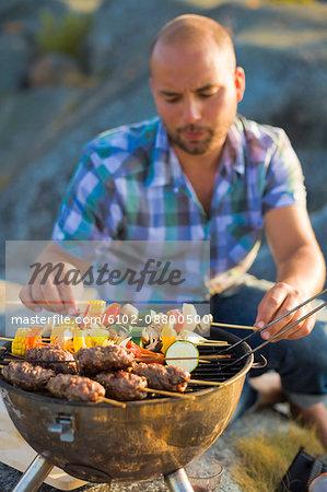 A man barbecuing, Stockholm archipelago, Sweden.