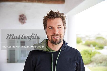 Portrait smiling brunette man wearing hoody on patio