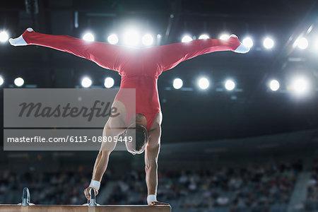 Male gymnast performing upside-down handstand on pommel horse