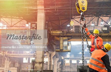 Steel workers operating crane in factory
