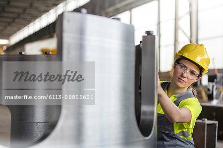 Female steel worker examining steel part in factory