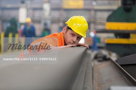 Steel worker examining steel in factory