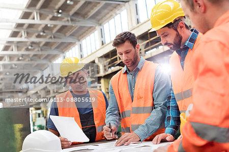 Steel workers and engineers meeting reviewing blueprints in factory