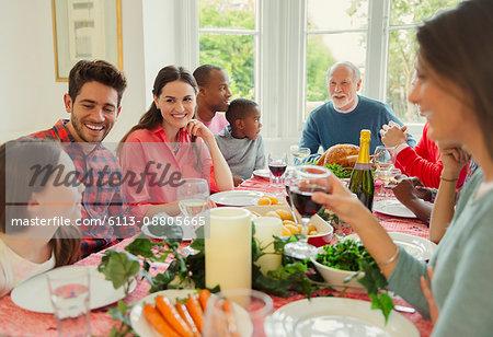 Multi-ethnic multi-generation family enjoying Christmas dinner at table